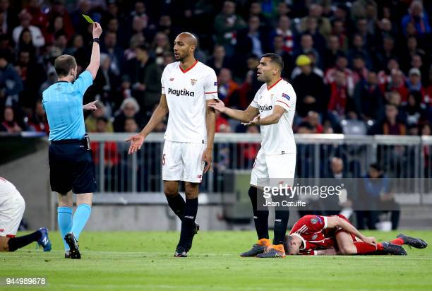Steven NZonzi of FC Sevilla receives a yellow card from referee William Collum of Scotland while Gabriel Mercado of FC Sevilla protests during the...