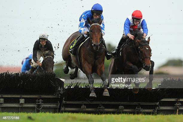 Steven Pateman riding Elms jumps the last hurdle with Arron Lynch riding Thubiaan in Race 3 the MRC $300000 jumps bonus maiden Hurdle during the...
