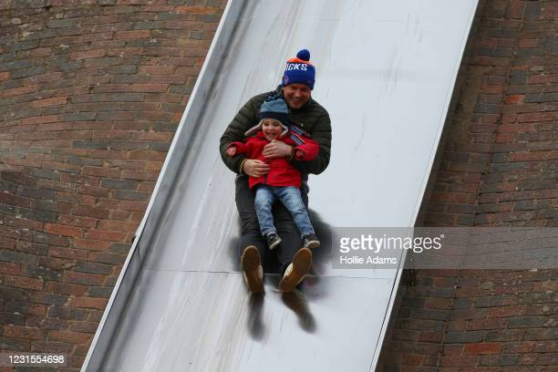 Steven Patrick and his son Jack go down a slide at Victoria Park playground on March 6, 2021 in London, England. Londoners are enjoying bright...