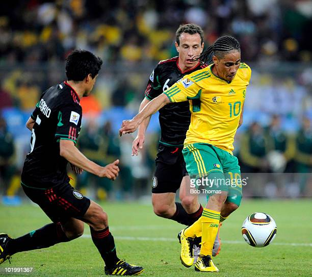 Steven Pienaar of South Africa is challenged by Gerardo Torrado and Ricardo Osorio of Mexico during the 2010 FIFA World Cup South Africa Group A...