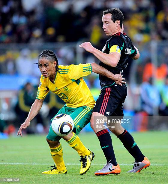 Steven Pienaar of South Africa shields the ball from Gerardo Torrado of Mexico during the 2010 FIFA World Cup South Africa Group A match between...