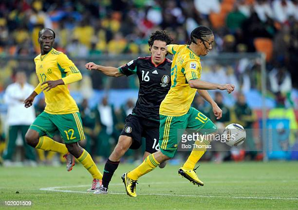Steven Pienaar of South Africa with the ball watched by Efrain Juarez of Mexico during the 2010 FIFA World Cup South Africa Group A match between...