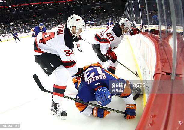 Steven Santini against New Jersey Devils Blake Coleman of the New Jersey Devils battle Mathew Barzai of the New York Islanders during their pre...