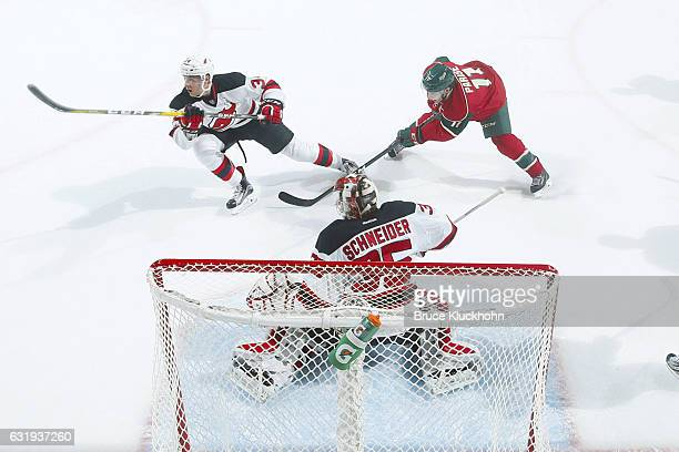 Steven Santini and goalie Cory Schneider of the New Jersey Devils defend their goal against Zach Parise of the Minnesota Wild during the game on...