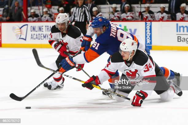 Steven Santini of the New Jersey Devils and John Tavares of the New York Islanders battle for the puck at the Barclays Center on March 31 2017 in...