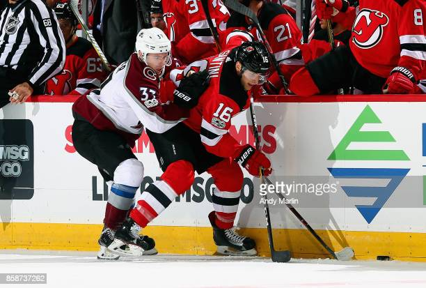 Steven Santini of the New Jersey Devils and JT Compher of the Colorado Avalanche battle for a loose puck during the Devils season opener at...