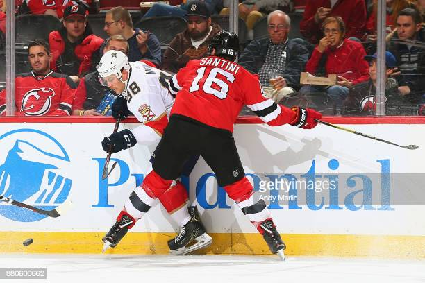 Steven Santini of the New Jersey Devils battles for the puck against Jamie McGinn of the Florida Panthers during the game at Prudential Center on...