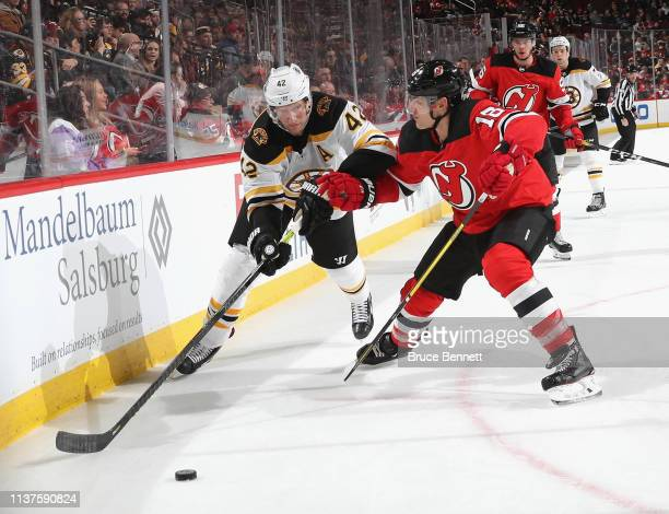 Steven Santini of the New Jersey Devils checks David Backes of the Boston Bruins at the Prudential Center on March 21 2019 in Newark New Jersey The...