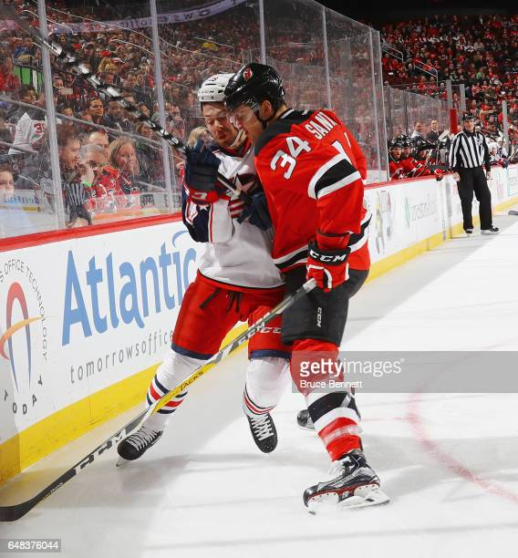 Steven Santini of the New Jersey Devils checks David Savard of the Columbus Blue Jackets during the first period at the Prudential Center on March 5...