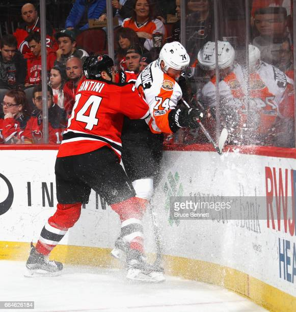 Steven Santini of the New Jersey Devils hits Mike Vecchione of the Philadelphia Flyers into the boards during the first period at the Prudential...
