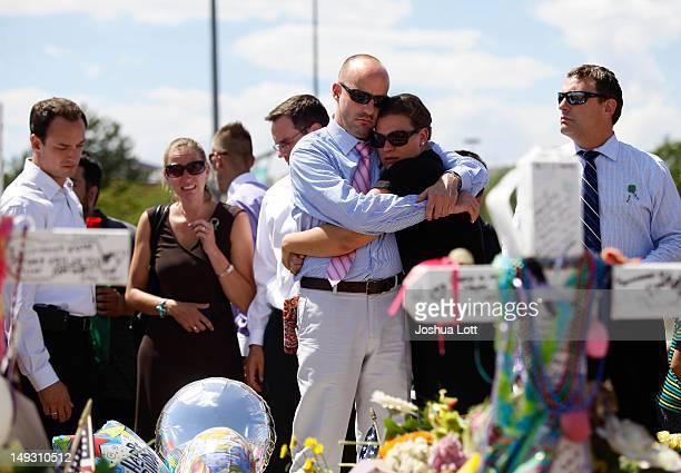 Steven Schwab cousin of Alex Sullivan embraces Karen Luke at a memorial across the street from the Century 16 movie theatreJuly 26 2012 in Aurora...