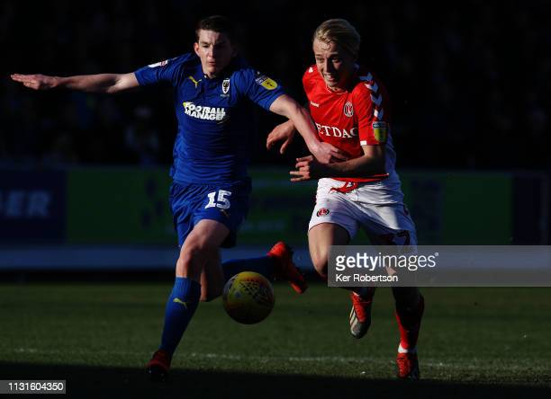 Steven Seddon of AFC Wimbledon and George Lapslie of Charlton Athletic challenge for the ball during the Sky Bet League One match between AFC...