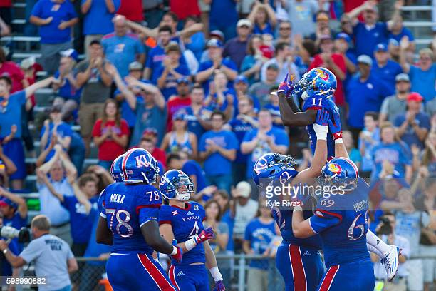 Steven Sims Jr #11 of the Kansas Jayhawks celebrates with his team after scoring a touchdown against the Rhode Island Rams defense in the first half...