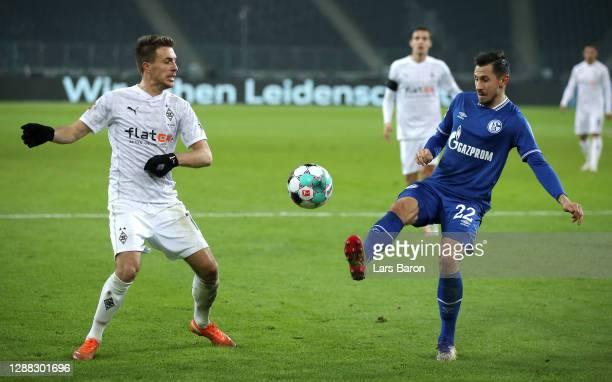 Steven Skrzybski of FC Schalke 04 is challenged by Patrick Herrmann of Borussia Monchengladbach during the Bundesliga match between Borussia...