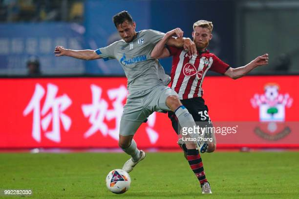 Steven Skrzybski of Schalke FC competes the ball with Josh Sims of Southampton FC during the 2018 Clubs Super Cup match between Schalke and...