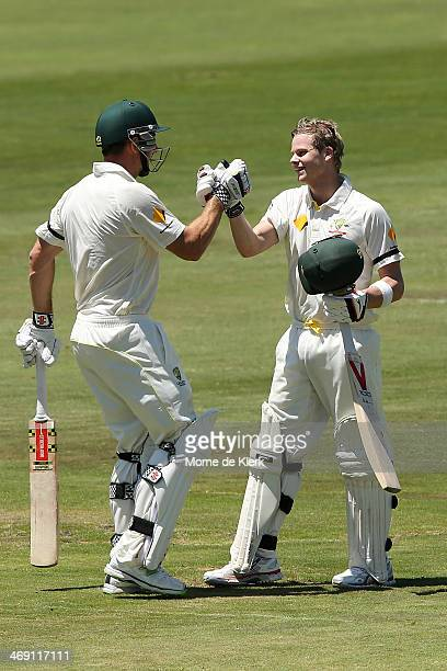 Steven Smith of Australia is congratulated by teammate Shaun Marsh after reaching 100 runs during day two of the First Test match between South...