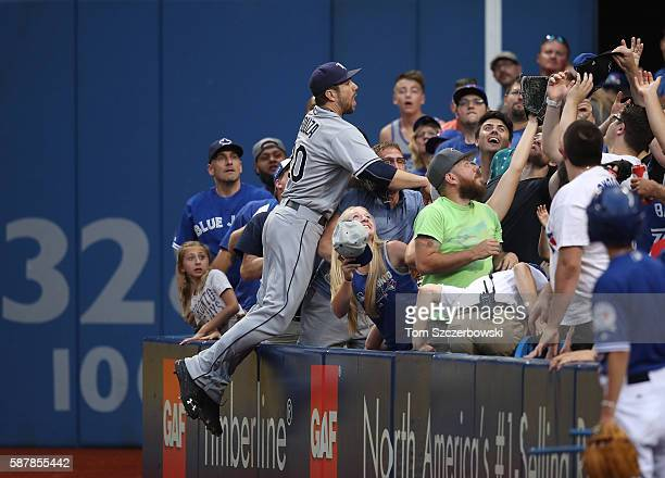 Steven Souza Jr #20 of the Tampa Bay Rays jumps into the crowd in pursuit of a foul ball in the second inning during MLB game action against the...