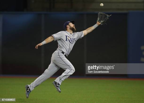 Steven Souza Jr #20 of the Tampa Bay Rays nearly misplays a single by Kevin Pillar of the Toronto Blue Jays in the first inning during MLB game...
