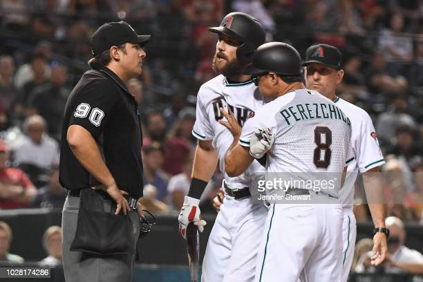 Steven Souza Jr #28 of the Arizona Diamondbacks is held back by third base coach Tony Perezchica while arguing a called strike three by umpire Mark...