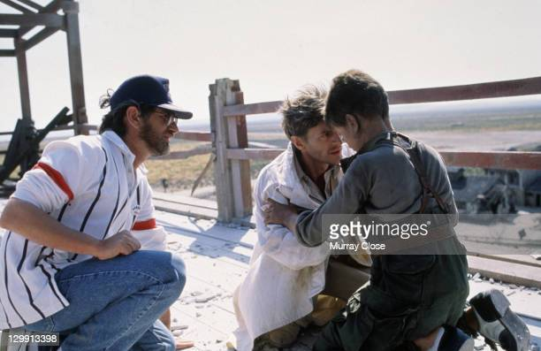 Steven Spielberg directs British actors Christian Bale and Nigel Havers in the rooftop scene from the film 'Empire of the Sun' 1987