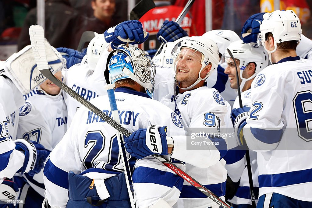 Steven Stamkos #91 and Evgeni Nabokov #20 of the Tampa Bay Lightning celebrate an overtime win against the Calgary Flames at Scotiabank Saddledome on October 21, 2014 in Calgary, Alberta, Canada.