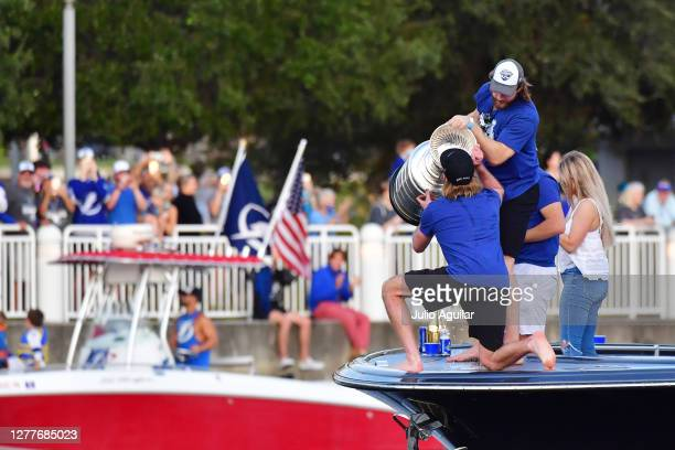 Steven Stamkos drinks out of the Stanley Cup on the held by Victor Hedman of the Tampa Bay Lightning at the Tampa Bay Lightning Victory Rally & Boat...
