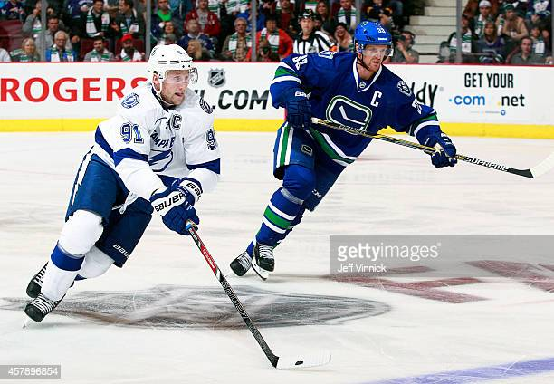 Steven Stamkos of the Tampa Bay Lightning and Henrik Sedin of the Vancouver Canucks skate up ice during their NHL game at Rogers Arena October 18...