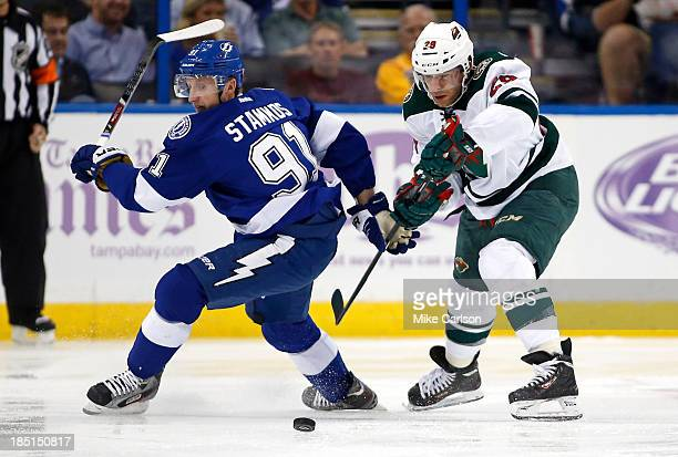 Steven Stamkos of the Tampa Bay Lightning and Jason Pominville of the Minnesota Wild battle for a loose puck at the Tampa Bay Times Forum on October...