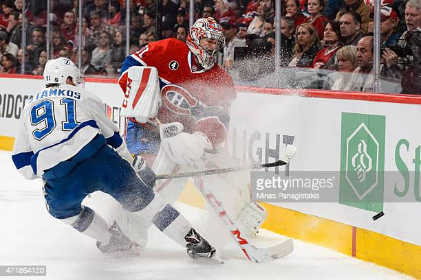 Steven Stamkos of the Tampa Bay Lightning challenges Carey Price of the Montreal Canadiens as he clears the puck against the boards in Game One of...