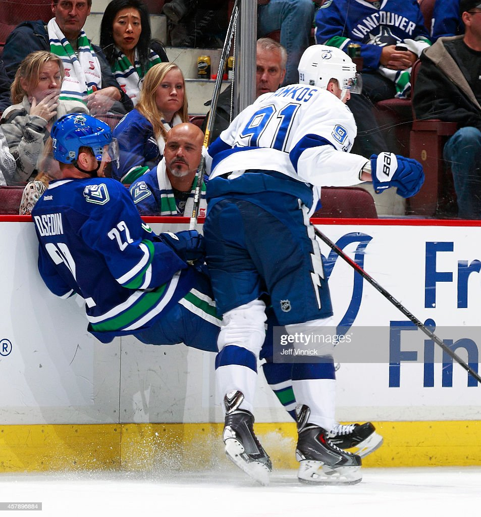 Steven Stamkos #91 of the Tampa Bay Lightning checks Daniel Sedin #22 of the Vancouver Canucks into the boards during their NHL game at Rogers Arena October 18, 2014 in Vancouver, British Columbia, Canada.