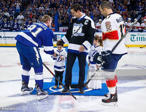 Steven Stamkos of the Tampa Bay Lightning gives the puck to Vincent Lecavalier's son after a ceremonial puck drop against Derek MacKenzie of the...