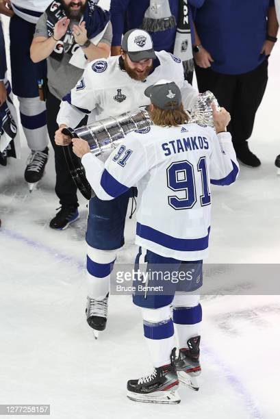 Steven Stamkos of the Tampa Bay Lightning hands off the Stanley Cup to Victor Hedman following the series-winning victory over the Dallas Stars in...