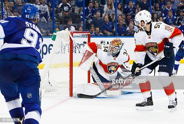 Steven Stamkos of the Tampa Bay Lightning shoots the puck for the game tying goal against goalie James Reimer and Jason Demers of the Florida...