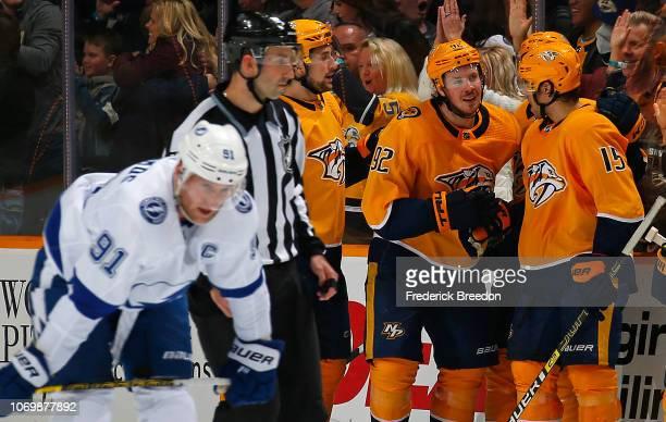 Steven Stamkos of the Tampa Bay Lightning skates by as Filip Forsberg and Craig Smith of the Nashville Predators congratulate teammate Ryan Johansen...