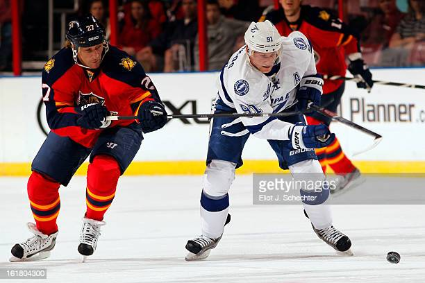 Steven Stamkos of the Tampa Bay Lightning skates with the puck against Alex Kovalev of the Florida Panthers at the BBT Center on February 16 2013 in...