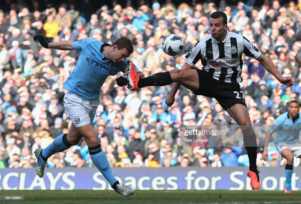 Steven Taylor of Newcastle United tries to block the header of Edin Dzeko of Manchester City during the Barclays Premier League match between Manchester City and Newcastle United at the Etihad Stadium on March 30, 2013 in Manchester, England.