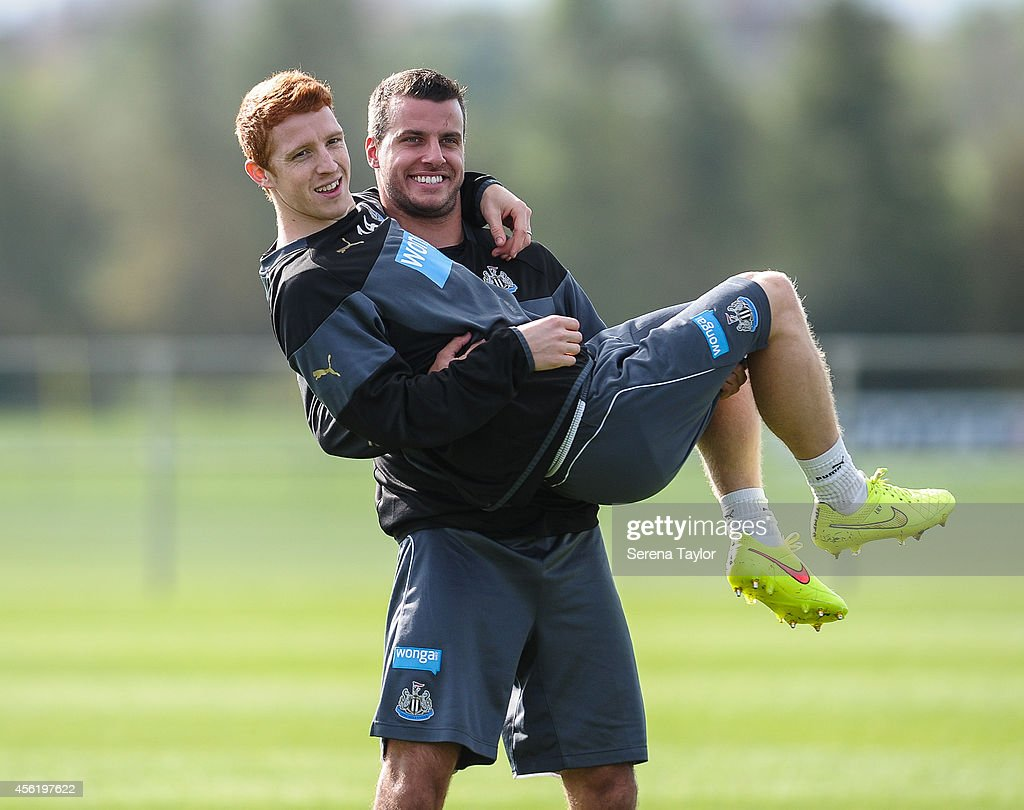 Steven Taylor (R) smiles whilst holding Jack Colback during a training session at The Newcastle United Training Centre on September 27, 2014, in Newcastle upon Tyne, England.