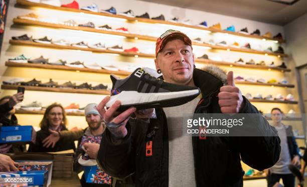 Steven the first customer to buy the Adidas / BVG trainers give thumbs up at the Overkill shoe store in Berlin on January 16 2018 The shoes set to...