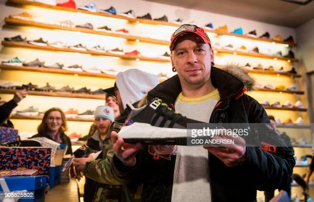Steven the first customer to buy the Adidas / BVG trainers holds his new shoes at the Overkill shoe store in Berlin on January 16 2018 The shoes set...