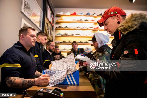 Steven the first customer to buy the Adidas / BVG trainers inspects his shoes at the Overkill shoe store in Berlin on January 16 2018 The shoes set...