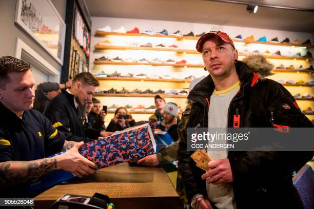 Steven the first customer to buy the Adidas / BVG trainers pays for his new shoes at the Overkill shoe store in Berlin on January 16 2018 The shoes...