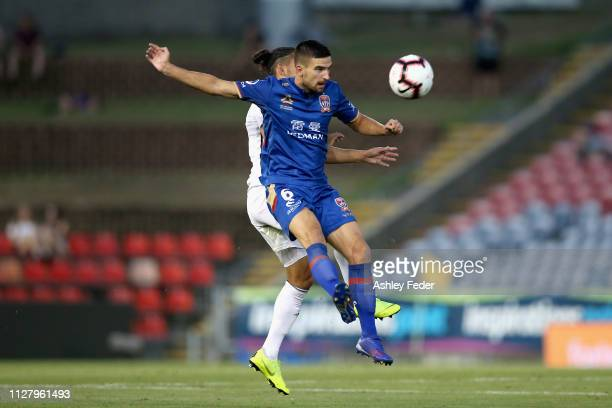 Steven Ugarkovic of the Newcastle Jets is contested by David Williams of Wellington Phoenix during the round 18 ALeague match between the Newcastle...
