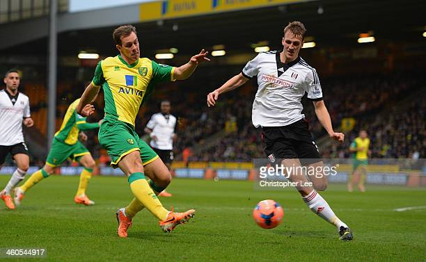 Steven Whittaker of Norwich shoots past Dan Burn of Fulham during the FA Cup sponsored by Budweiser Third Round match between Norwich City and Fulham...