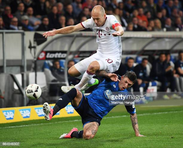 Steven Zuber of 1899 Hoffenheim tackles Arjen Robben of Bayern Munich during the Bundesliga match between TSG 1899 Hoffenheim and Bayern Muenchen at...