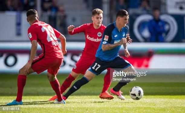 Steven Zuber of Hoffenheim is challenged by Guillermo Varela of Frankfurt during the Bundesliga match between TSG 1899 Hoffenheim and Eintracht...