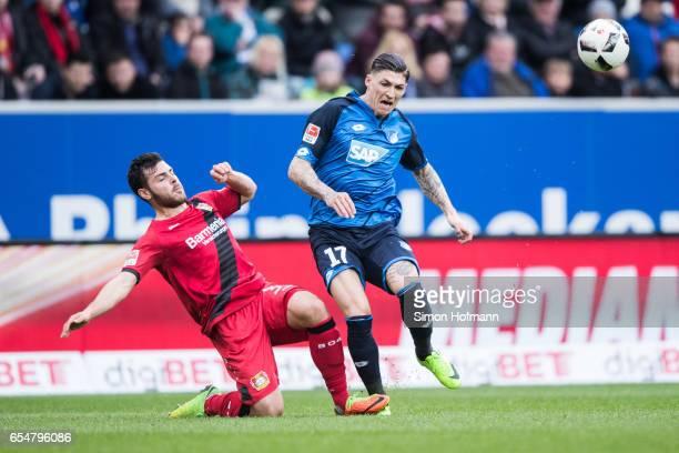 Steven Zuber of Hoffenheim is challenged by Kevin Volland of Leverkusen during the Bundesliga match between TSG 1899 Hoffenheim and Bayer 04...