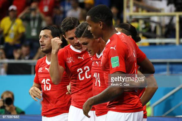 Steven Zuber of Switzerland celebrates with team mates Fabian Schaer and Manuel Akanji after scoring his team's first goal during the 2018 FIFA World...