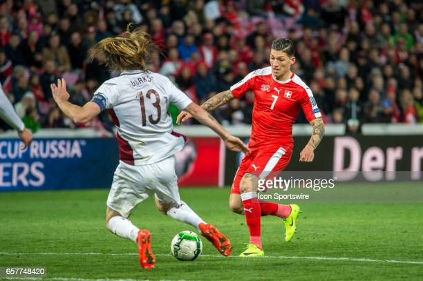 Steven Zuber vies with Kaspars Gorkss during the World Cup Qualifiers group match between Switzerland and Latvia on March 25 at Stade de Geneva in...