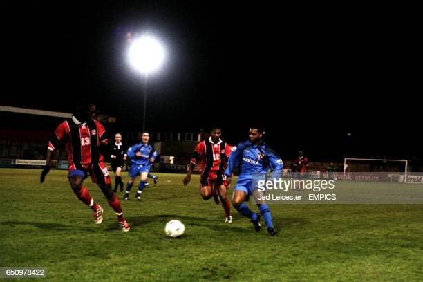 Stevenage Borough's Sam McMahon is shadowed by Trinidad and Tobago's Brent Sancho and team mate Brent Rahim
