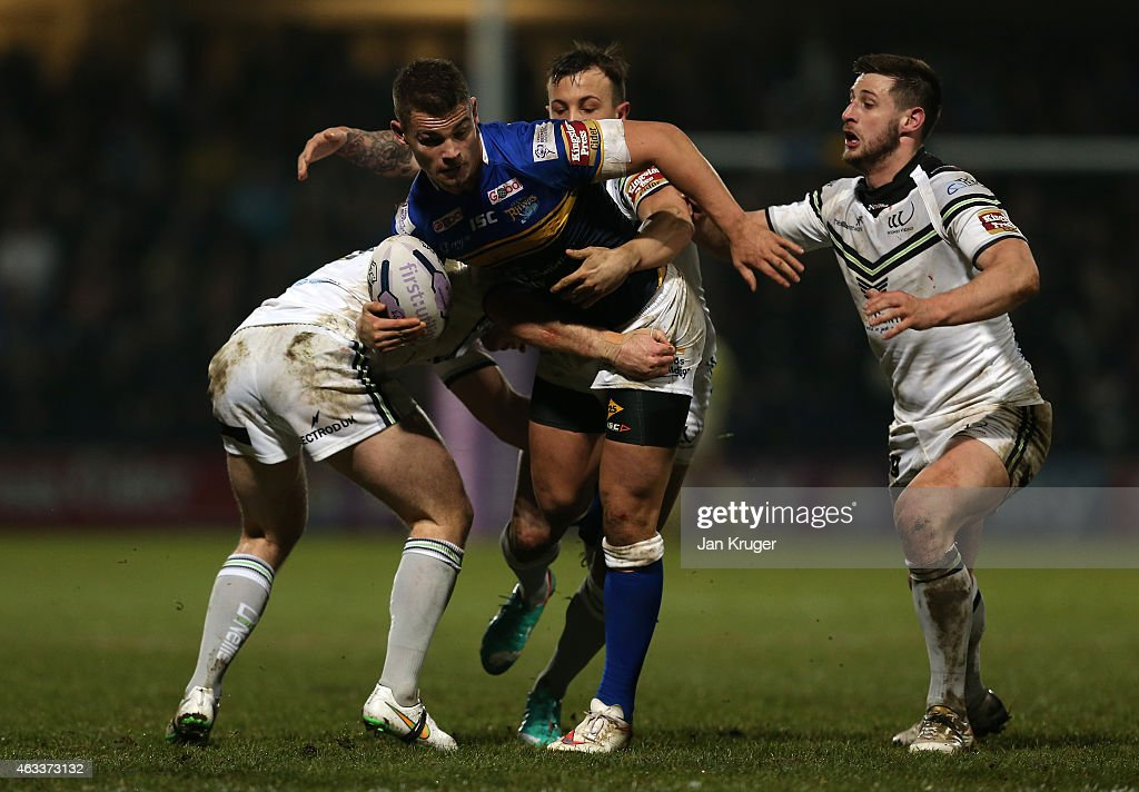 Stevie Ward of Leeds Rhinos crashes into Cameron Phelps and Danny Craven of Widnes Vikings during the First Utility Super League match between Leeds Rhinos and Widnes Vikings at Headingley Carnegie Stadium on February 13, 2015 in Leeds, England.